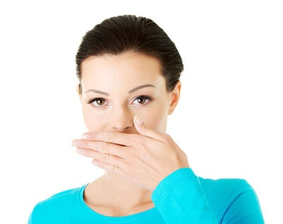 A woman embarrassed by her smile covers her mouth